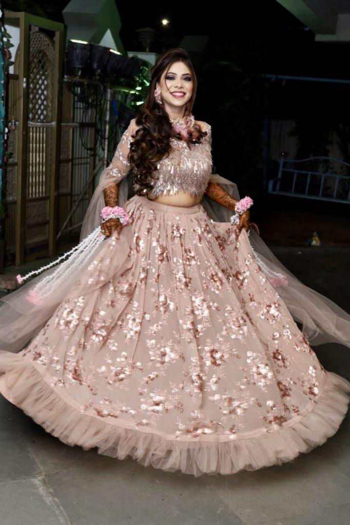 Bride twirling pink shimmery floral lehenga for Mehendi ceremony at Destination wedding in Karjat