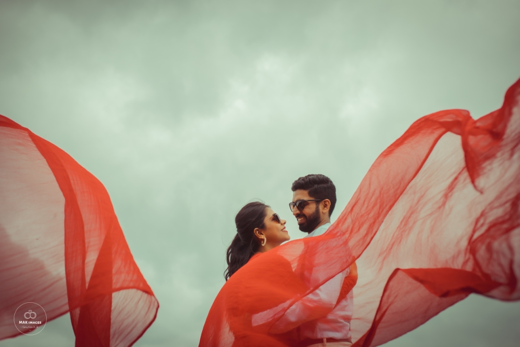 Cute Bollywood style Pre Wedding Picture of Pooja & Mohit with a flowing Red Dupatta