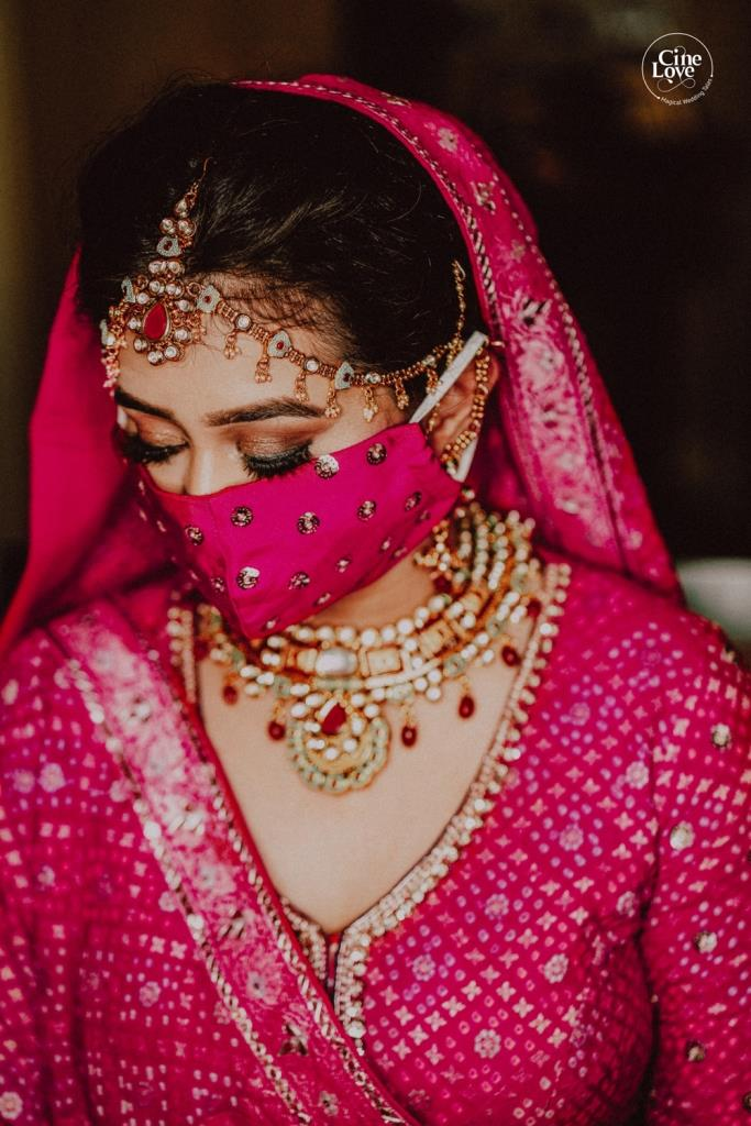 Ayushi's bridal solo portrait picture in a beautiful Pink Lehenga with coordinating embellished mask