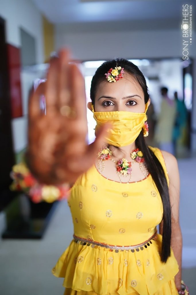 Sakshi dressed in yellow outfit with coordinating mask for her small Intimate home wedding in Lockdown