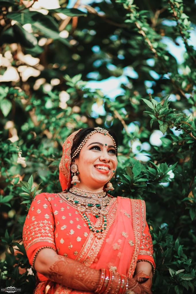 Riddhi glowing in her red bridal lehenga and green jewellery set at her intimate wedding in lockdown