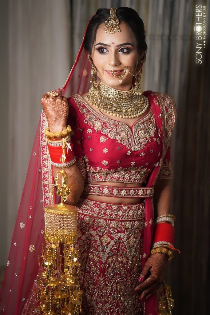 Portrait of Sakshi looking majestic in her designer red bridal lehenga at one of the best intimate weddings in lockdown