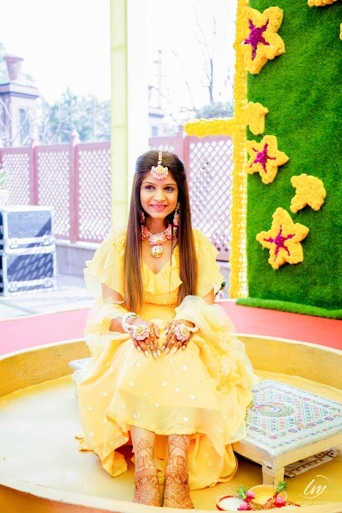 Akansha adorned in a lovely ruffled yellow blouse and long skirt for her Haldi at Le Meridien Jaipur