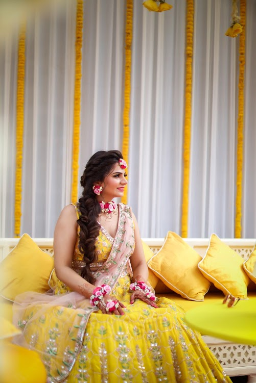 Aakriti in an elegant yellow lehenga by Akilah with a blush pink dupatta for her Summer-Themed Haldi at Destination Wedding in Gurgaon