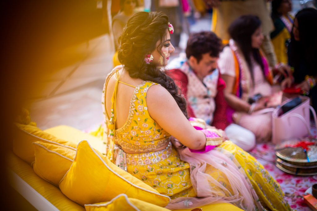 Aakriti in a beautiful yellow lehenga, fishtail braid and pink floral jewellery for the haldi ceremony of her ITC Grand Bharat wedding