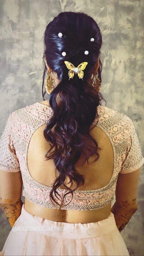 A bride in a pastel peach outfit & tight low ponytail with curly ends embellished with pearls & butterfly hair accessories giving beautiful bridal hairstyle ideas for an engagement ceremony