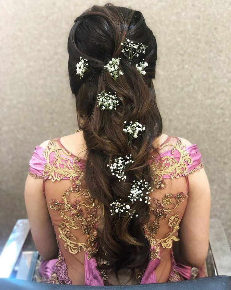 A bride in messy princess braid hairstyle for engagement ceremony with scattered baby breath flowers