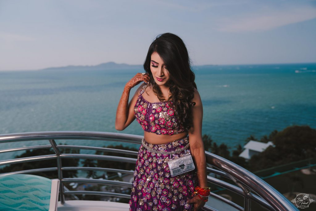 Bride Nikita in embellished purple outfit & open hair hairstyle with soft loose curls at the ends giving beautiful bridal hairstyle ideas for an engagement ceremony