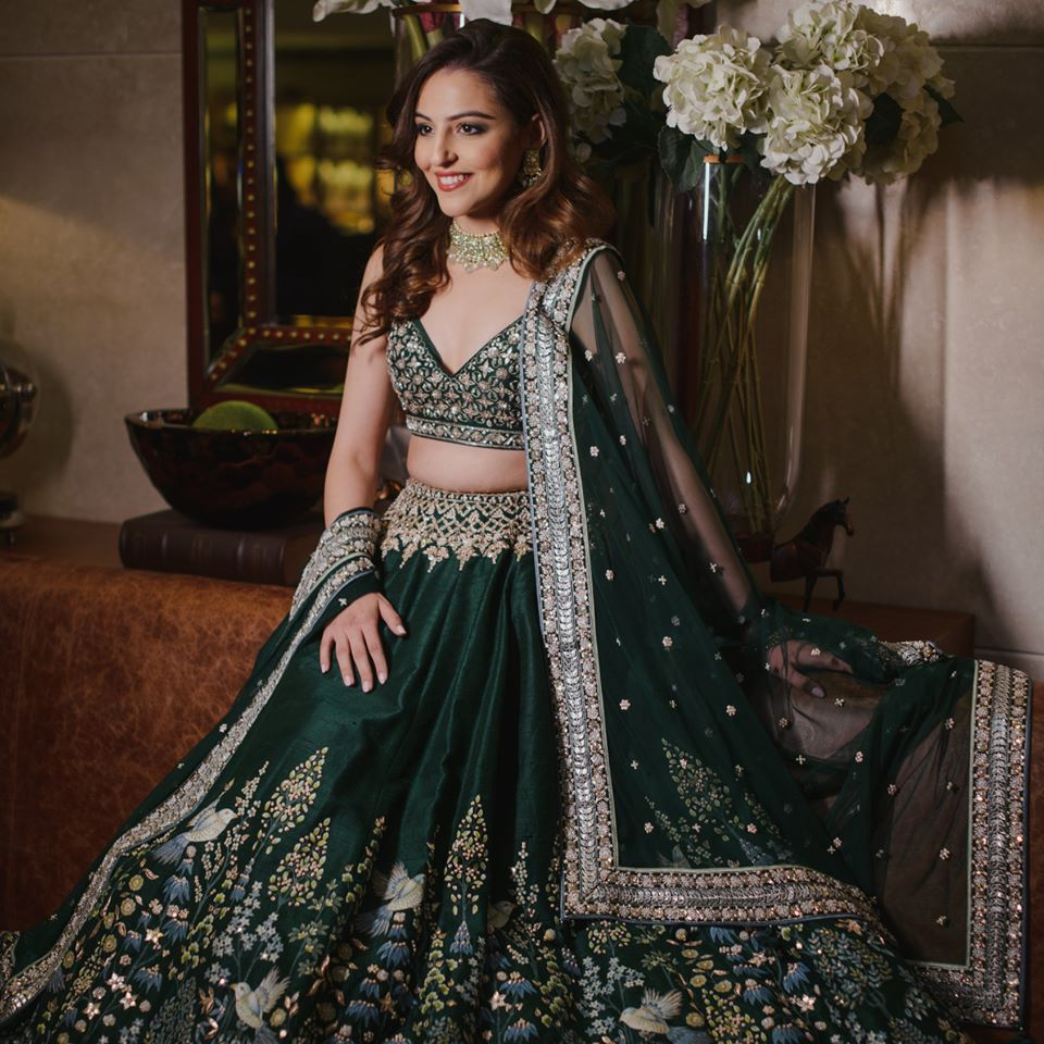 A beautiful bride in dark green anita dongre lehenga, soft nude makeup & open hair with outward curls giving beautiful bridal hairstyle ideas for an engagement ceremony