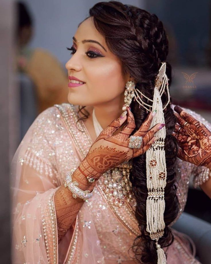 A beautiful bride in pink shimmery lehenga & side fishtail braid with twisted sectioned front braids & pearl hair jewelry