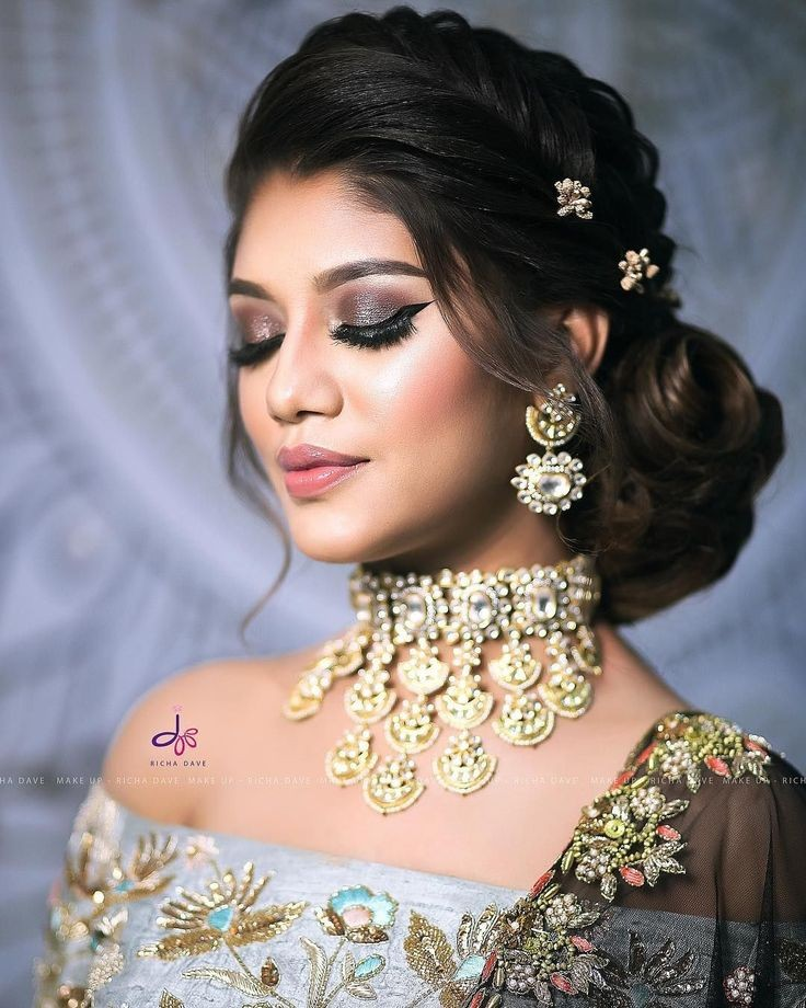 A bride in dramativ shimmery makeup look & hairdo with front braid & wavy bun adorned with tiny flower hair accessories for an engagement ceremony