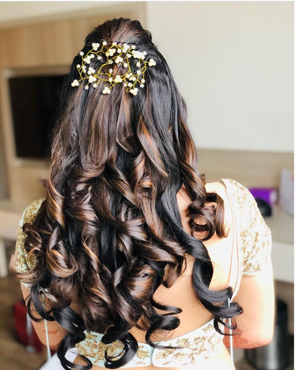 A bride wearing half up half down hairstyle with highlighted cascading curls & pearl hair comb pin for her roka ceremony