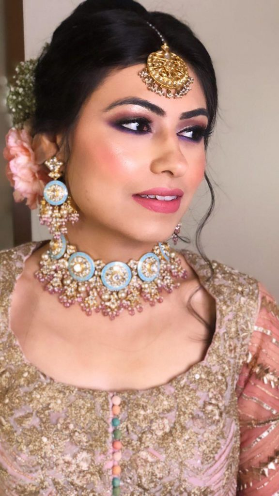 A bride in pink gold outfit, nude soft pink makeup look & a mid parted floral braid with pink roses & baby braeth flowers for her roka ceremony