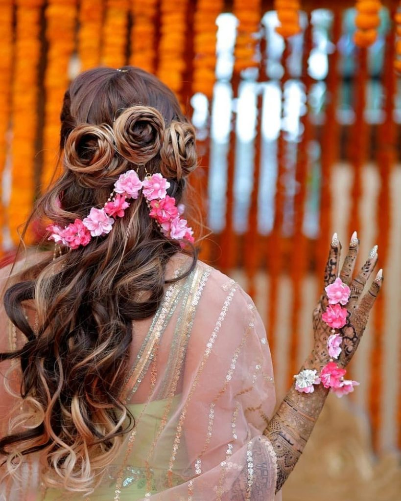 A bride in pink white floral jewelry & highlighted cascading curls with three rose braids at the back & adorned with fkoral hair jewelry giving beautiful bridal hairstyle ideas for a mehendi ceremony