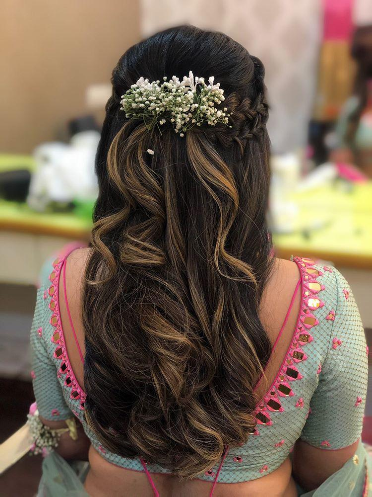 A bride in open layered crown braided golden highlighted curls with baby breath flower clip giving beautiful bridal hairstyle ideas