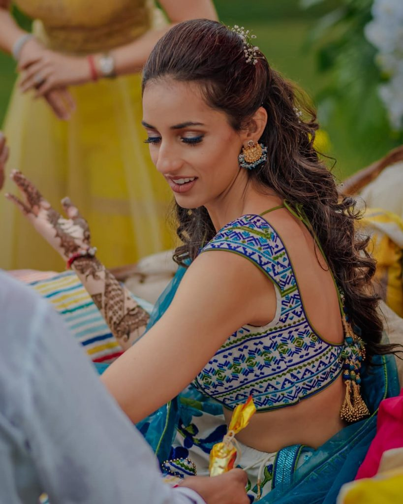 A bride in printed blue, white, green lehenga & simple half up half down hairstyle with baby breath floral clip giving beautiful bridal hairstyle ideas for a mehendi ceremony