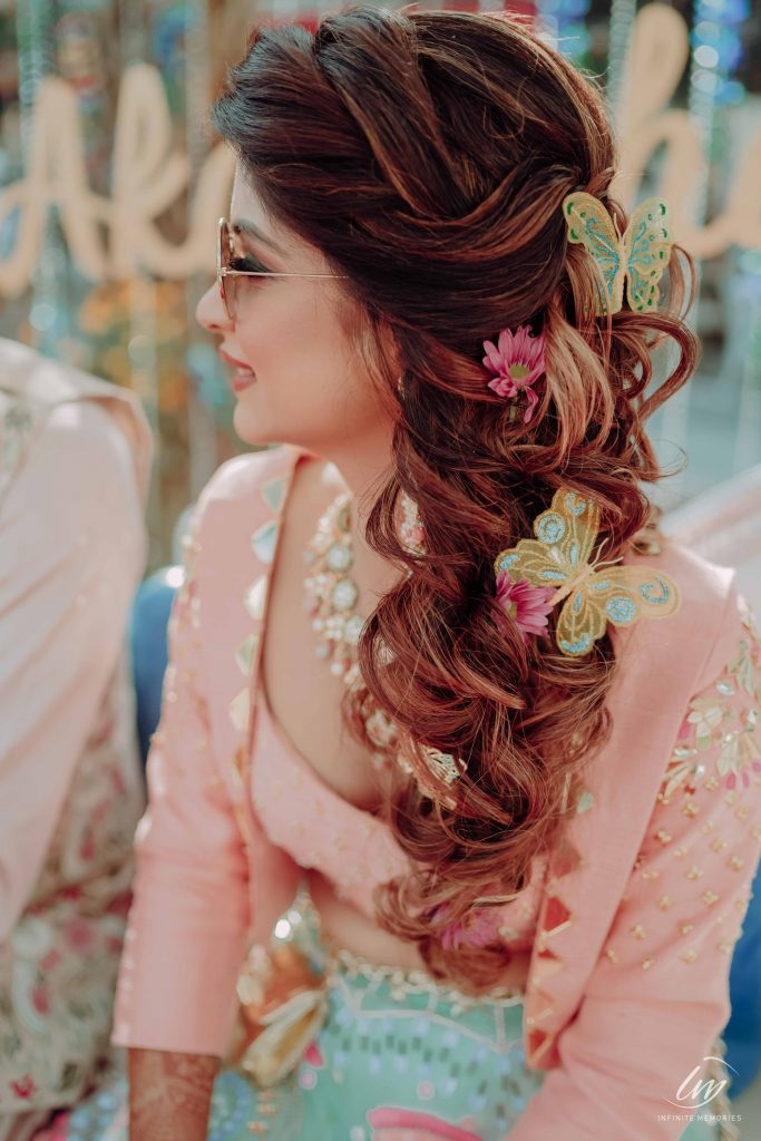 Bride Akansha in a pink blue indo western outfit & twisted messy side braid with pink daisies & butterfly hair accessories giving beautiful bridal hairstyle ideas