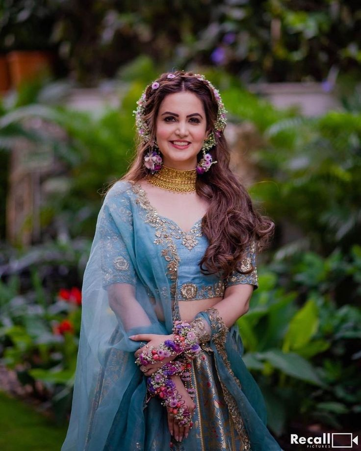 An adorable bride in blue lehenga, golg choker, floral jewelry & mid parted open wavy hair with a floral headband giving beautiful bridal hairstyle ideas for a mehendi ceremony
