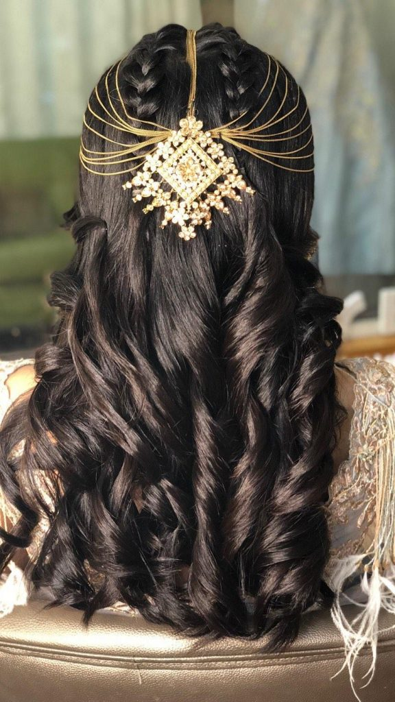 A bride wearing front braided cascading curls with delicate gold hair jewelry giving beautiful bridal hairstyle ideas for a cocktail ceremony