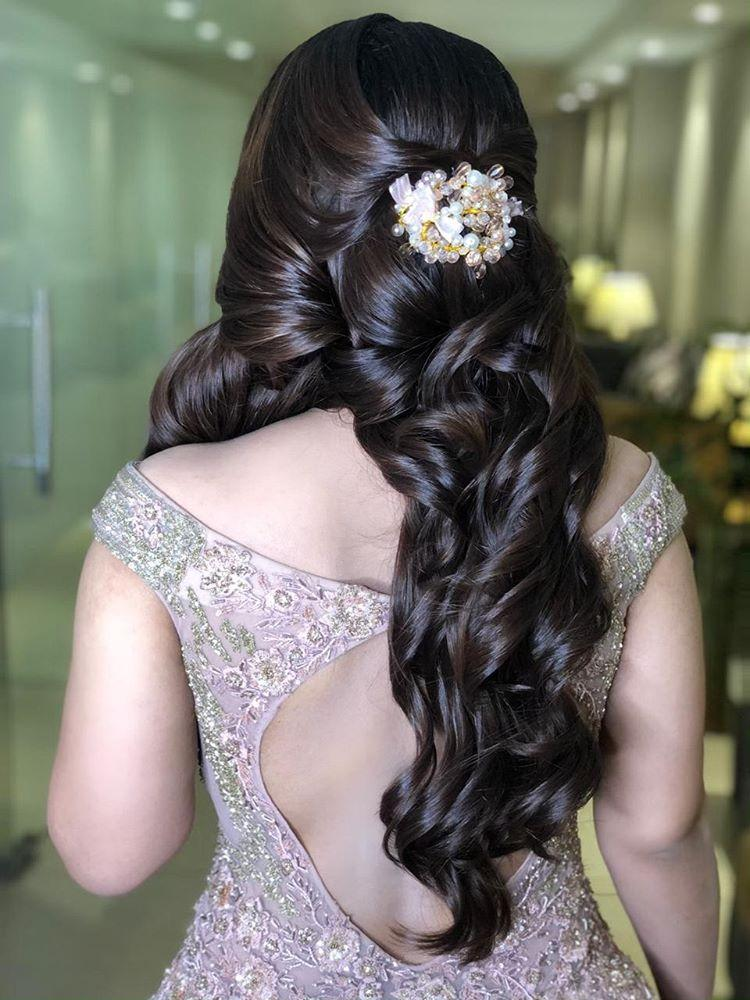 A bride in silver cocktail gown & voluminous thick curls hairstyle giving beautiful bridal hairstyle ideas