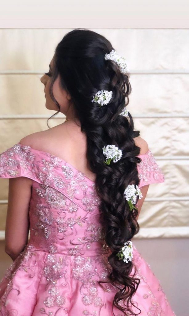 A bride in pink princess gown & a messy princess braid hairstyle with scattered baby breath flowers