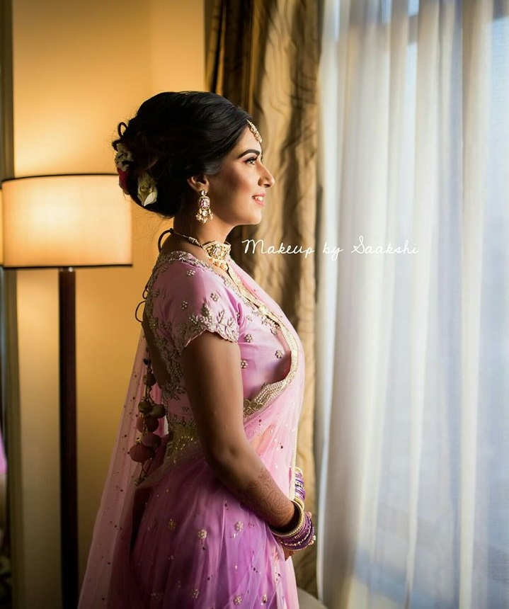 A bride in violet pink lehenga & bouffant bun hairstyle adorned with white & red roses giving beautiful bridal hairstyle ideas for sangeet