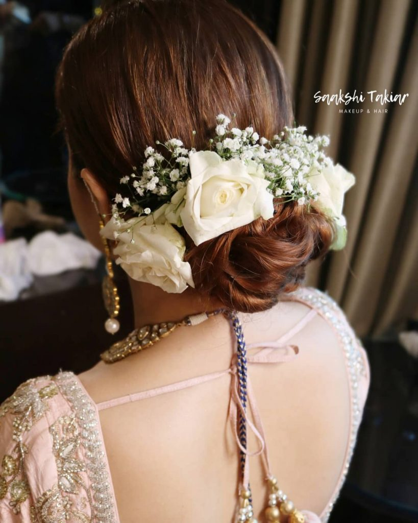 A bride in a braided low bun with white roses & baby breath flowers