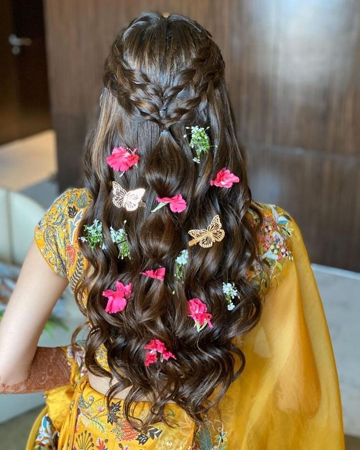 A bride in yellow embroidered lehenga & crown braided cascading curls hairstyle with floral petals & butterfly hair accessories