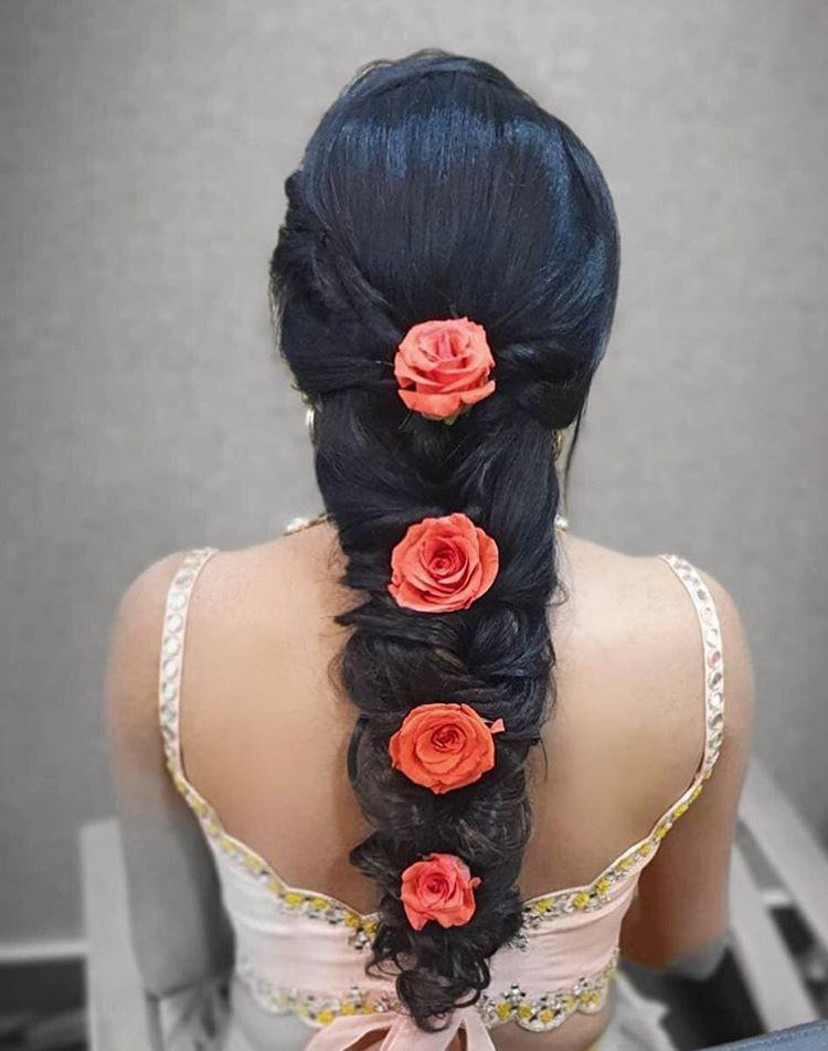 An Indian bride in a back fishtail braid with cascading peach color roses giving beautiful bridal hairstyle ideas