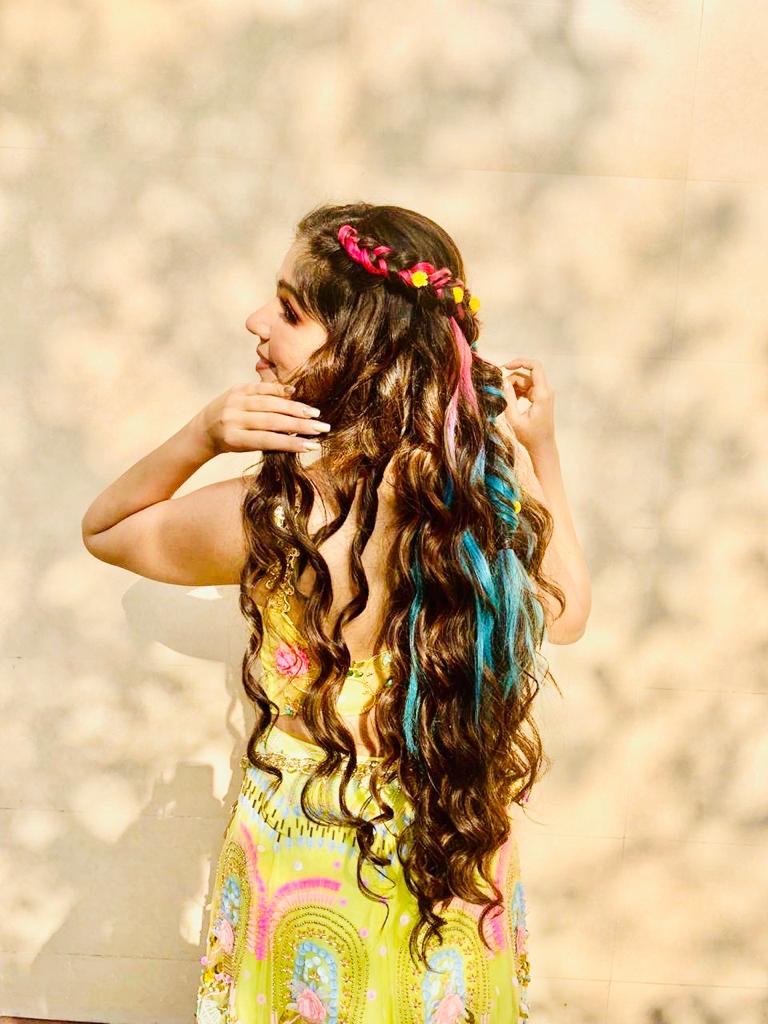 Harsha in yellow green haldi outfit & side swept braided cascading curls hairstyle with colorful hair extensions