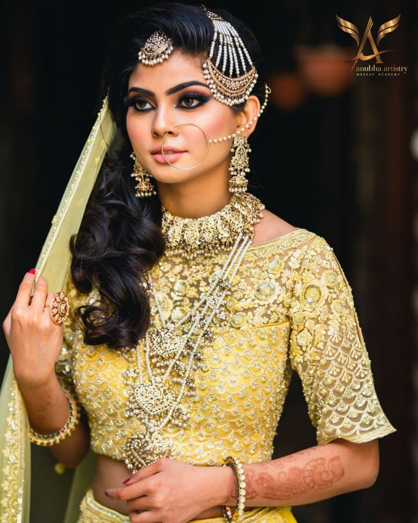 A bride in Pakistani bridal look with a lemon yellow lehenga & side flipped hairstyle with vintage curls & traditional passa hair jewelry giving beautiful bridal hairstyle ideas