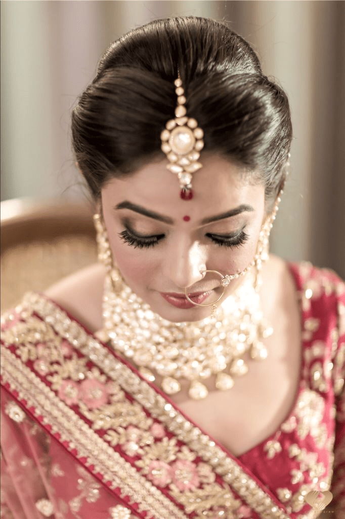 A bride in red & gold lehenga and sectioned front puffs hair bun giving beautiful bridal hairstyle ideas