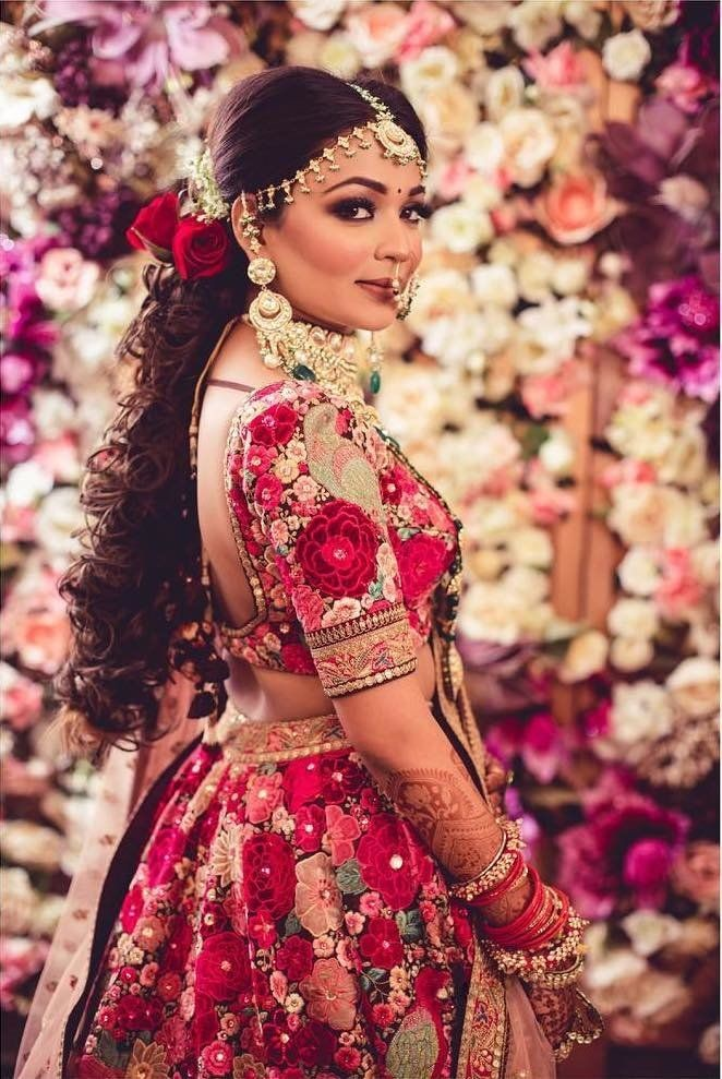 A beautiful bride in Sabyasachi's dil guldasta lehenga & two side front puffed curly ponytail with red roses & baby breath flowers giving beautiful bridal hairstyle ideas