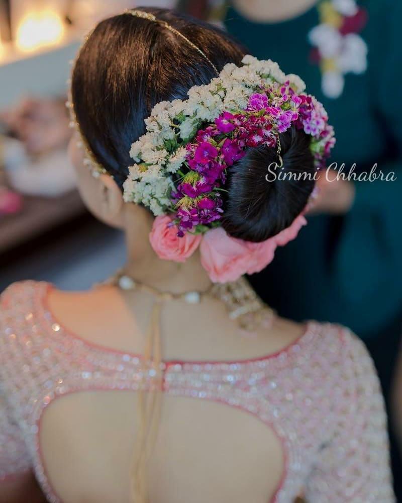 A bride in clean donut bun with white, purple flowers & baby pink roses giving beautiful bridal hairstyle ideas