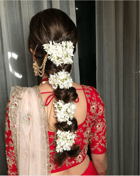 A bride in red & white lehenga, waterfall earrings & a bubble braid with mogra flowers giving beautiful bridal hairstyle ideas