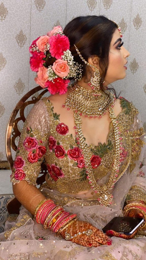 A gorgeous bride in floral bun with multi-color flowers & a shimmery white, gold & red embroidered bridal lehenga giving beautiful bridal hairstyle ideas