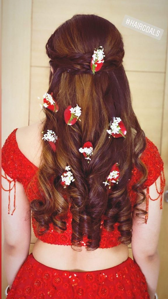 A bride in braided cascading curls with rose petals & baby breath flowers giving beautiful bridal hairstyle ideas