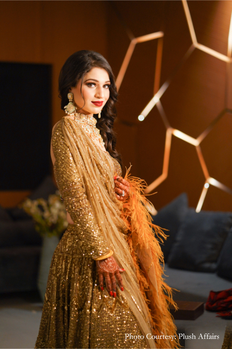 Aytal in gold shimmer outfit, elaborate Kundan jewelry & side swept curls giving beautiful bridal hairstyle ideas