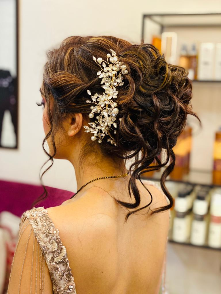 A bride in curly messy updo embellished with swarovski hair comb pin giving beautiful bridal hairstyle ideas
