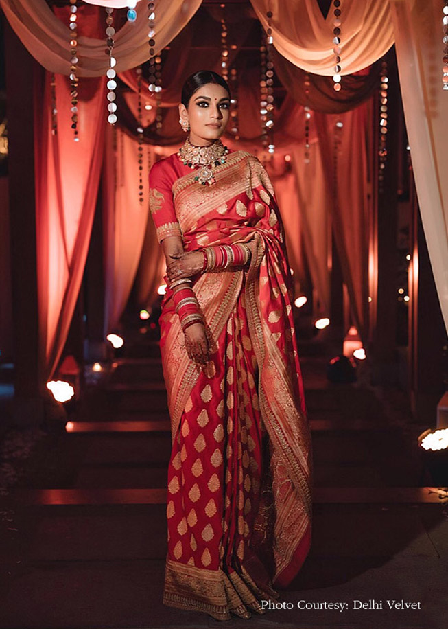 A stunning bride in red sabyasachi saree & sleek fun with sabyasachi jewelry Nitika in red reception gown & loose tied wavy hairdo giving beautiful bridal hairstyle ideas