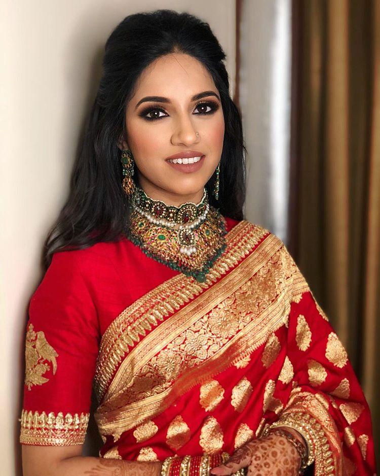 Bride in red sabyasachi saree & half tie hairstyle giving beautiful bridal hairstyle ideas
