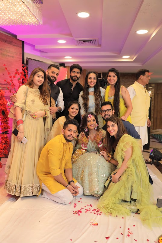 Group Picture of Nishtha with her friends and family captured at her Crowne Plaza Gurgaon Wedding's Haldi Party