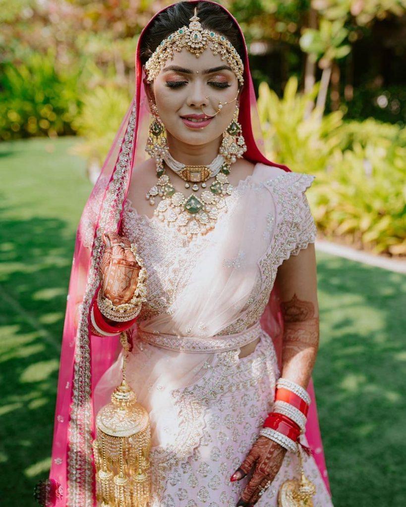 Bride Somi solo portrait in a pink wedding lehenga & pearl kundan jewellery with beautiful gold kaleeras & nude pink makeup look