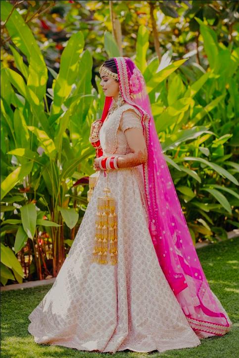 Somi looking beautiful in her baby pink bridal lehenga for her Mayfair Raipur Wedding