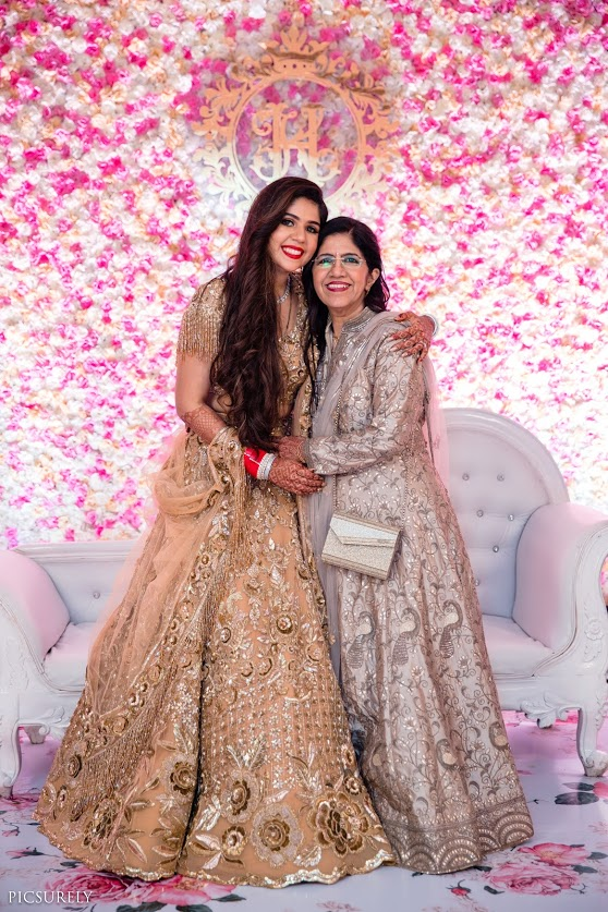 Harsha and her mother in coordinated golden outfits for her reception party post Sea Princess Juhu Wedding