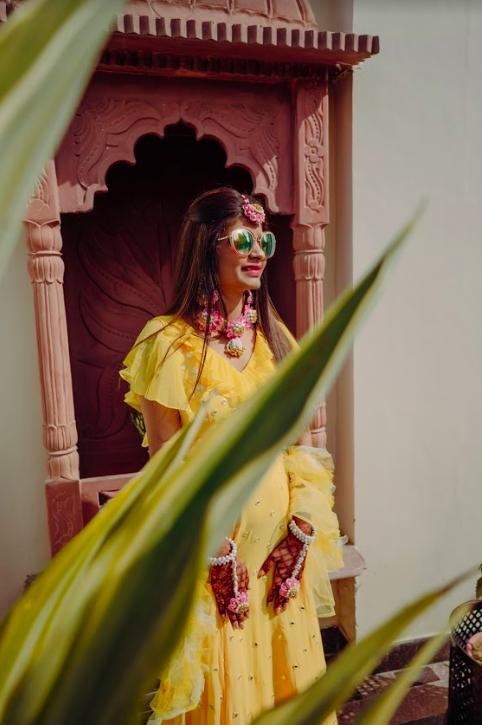 Akansha looking stunning in her yellow lehenga and floral jewellery for her Royal Marwari Wedding's Haldi Party at Le Meridien Jaipur