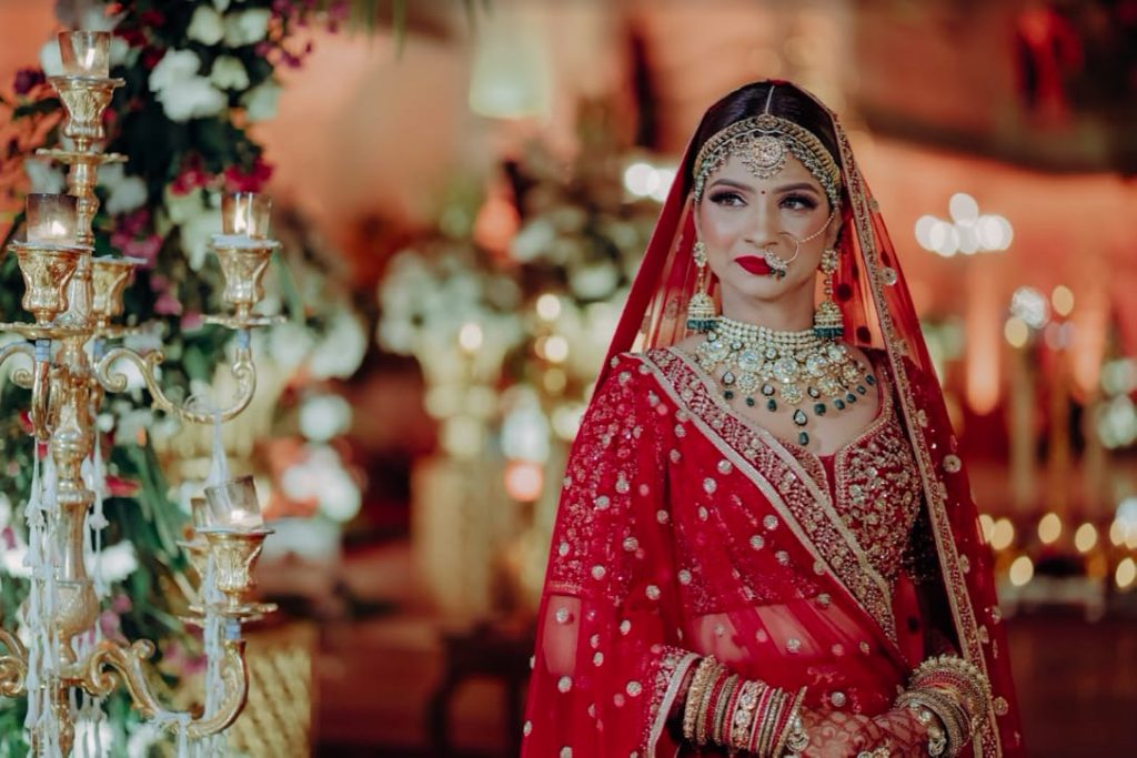 Akansha glowing in her red Sabyasachi lehenga at her luxury wedding in Jaipur