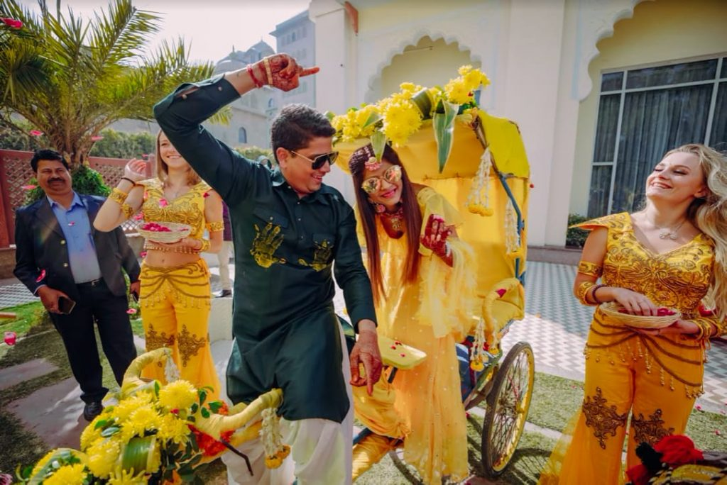 Unique Entry to Haldi Ceremony in a quirkily decorated rickshaw and flower shower by Russian girls