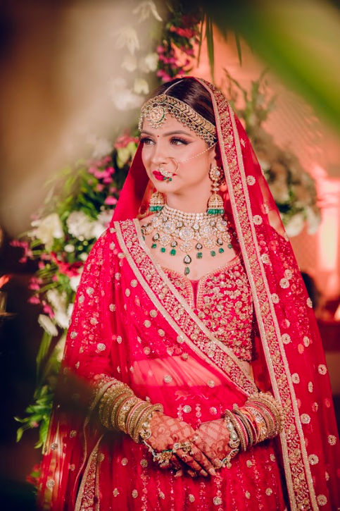 Candid Portrait of Akansha in her Red Sabyasachi Bridal Lehenga and traditional Marwari Jewellery shot at The Gulmohar Jaipur