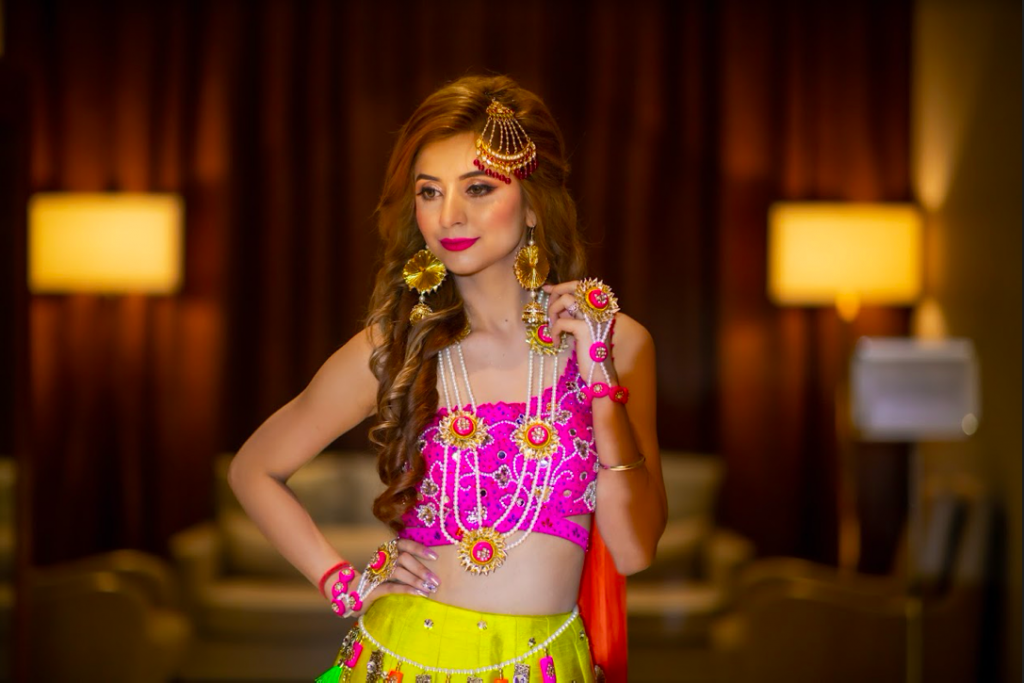 Kanika in a vibrant pink and yellow lehenga for her Mehendi Party before the grand Fairmont Ajman Wedding